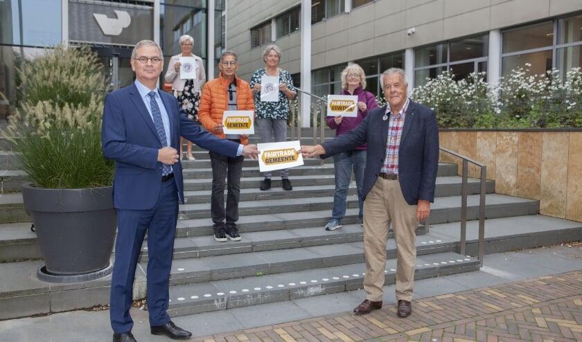 <p>Wethouder Marco Verloop (links) ontvangt het juryrapport van Wim Bakker en aan aantal vrijwilligers van Veenendaal4Fair.</p>