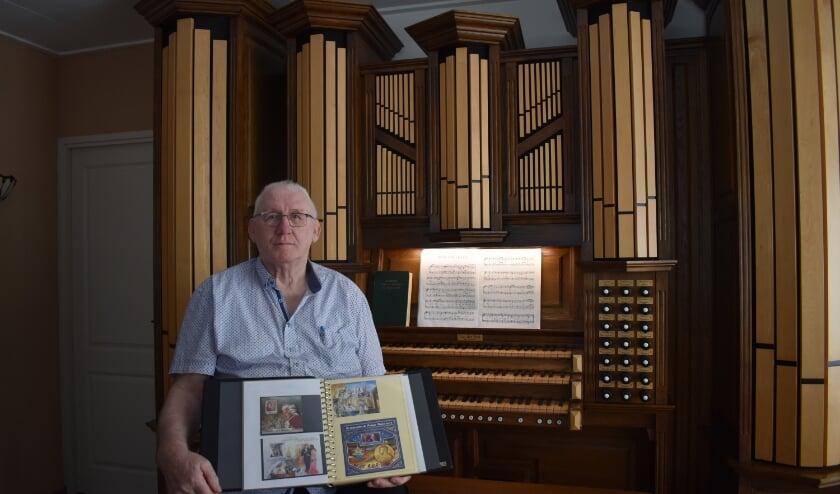 Hans Timmerman met zijn postzegelalbum voor het zelfgemaakte orgel. (Foto: Van Gaalen Media)