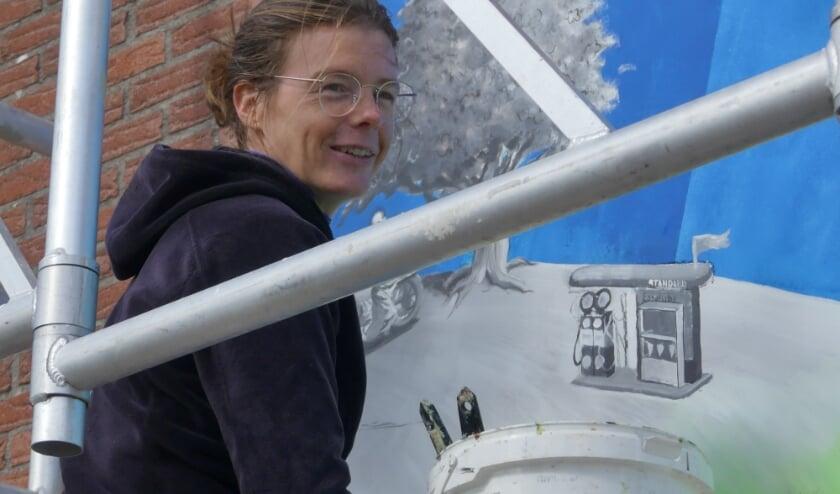 <p>Dorien Wagenaar schildert de zijmuur van rijwielhandel Van Balveren in Silvolde. (foto: Charlotte Wolters)</p>