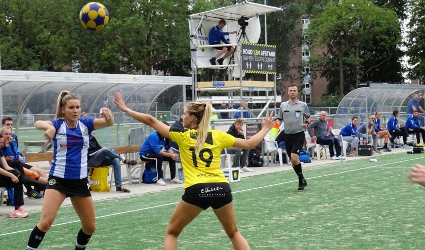 KV Wageningen speelster Michelle van den Tempel (links) in duel met een speelster van Dalto. Rechts naast de grensrechter kijkt haar coach, Ron Steenbergen, gespannen toe.