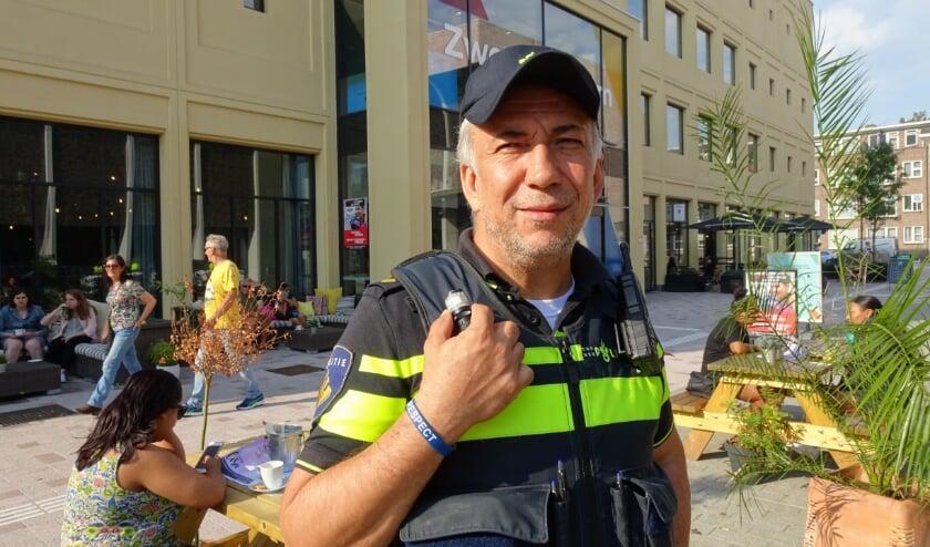 <p>Sefa Aijali, wijkagent Zuidplein toont het polsbandje #Respect van oud voor jong. Foto: Joop van der Hor</p>