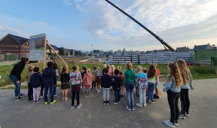 De kinderen kijken naar de bouw van de school