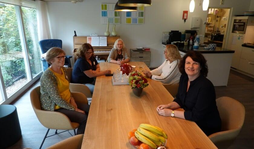 <p>Marijke Rekers (links) en Marriet Aalberts (rechts) met vrijwilligsters in de woonkamer van het hospice. </p>