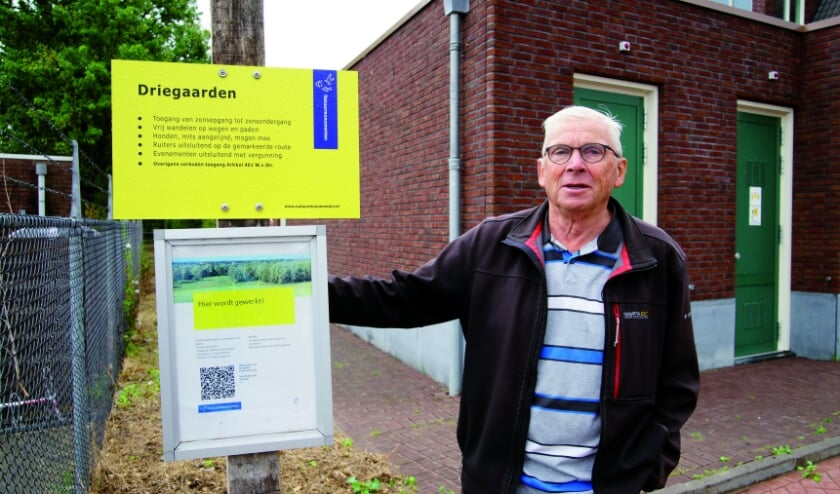 """Bas Brugmans bij het bordje dat de ingang van natuurgebied Driegaarden markeert: """"Omdat je met wandelen flink in beweging bent, slaap je meestal ook goed."""""""