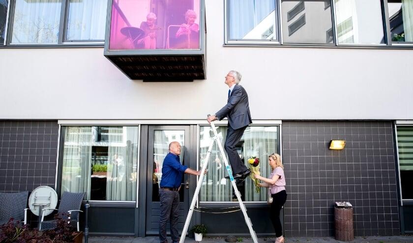<p>Burgemeester Theo Weterings deelt via een ladder bloemen uit aan ouderen in een verzorgingshuis</p>