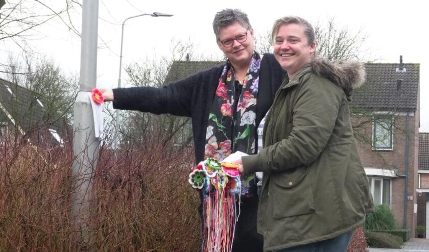 """<p>Vriendinnen Haziena van Ee en Gitta Vernooij hangen de gehaakte bloemen op in de Bommelerwaard. """"We hangen ze op van Kerkdriel tot Poederoijen en van Nieuwaal tot Nederhemert.""""&nbsp;</p>"""