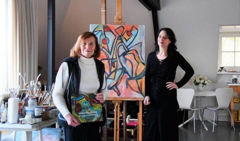 Henny Brusselers in haar atelier aan huis, samen met Maartje Meerman, een van de samenstellers van het imposante boek over haar werk en leven.