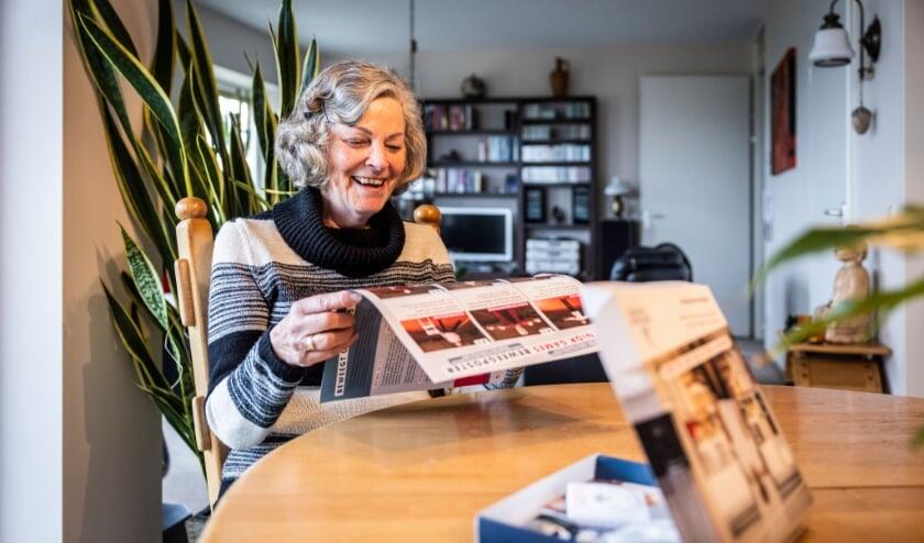 <p>Mevrouw Matena bekijkt de oefeningen op de Beweegposter.</p>