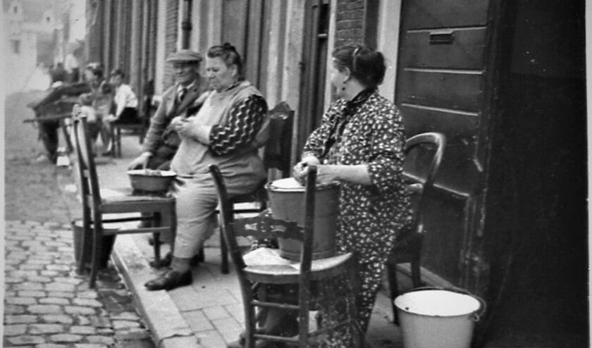 <p>Uit de collectie van het Volksbuurtmuseum; 1940: In de Koningstraat schillen huisvrouwen de aardappels voor het avondeten.</p>