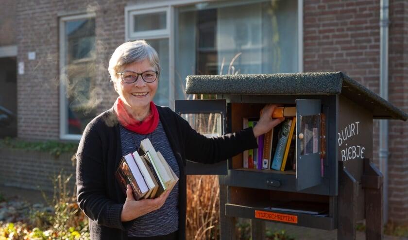 <p>Truus Vorstenbosch bij haar Buurt Bieb die regelmatig door wandelaars wordt bezocht.&nbsp;</p>