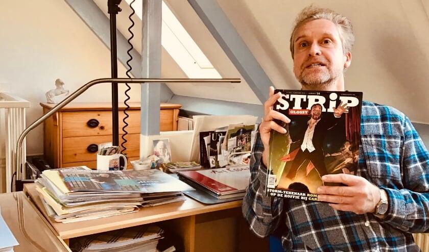 <p>Frits van Loenen op zijn werkplek met de StripGlossy waarin hij meedoet aan de battle. Thema is De TV-Kantine. Vandaar op de cover presentator én gastredacteur van dit nummer Carlo Boszhard. (Eigen foto).</p>