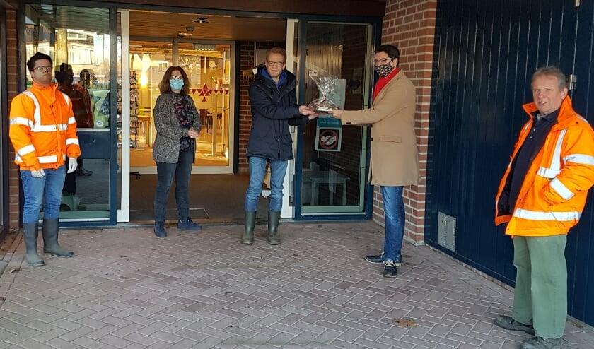 <p>SP-fractievoorzitter Martijn Stoutjesdijk overhandigt een schaal bonbons aan enkele cliënten van Harmonika.</p>