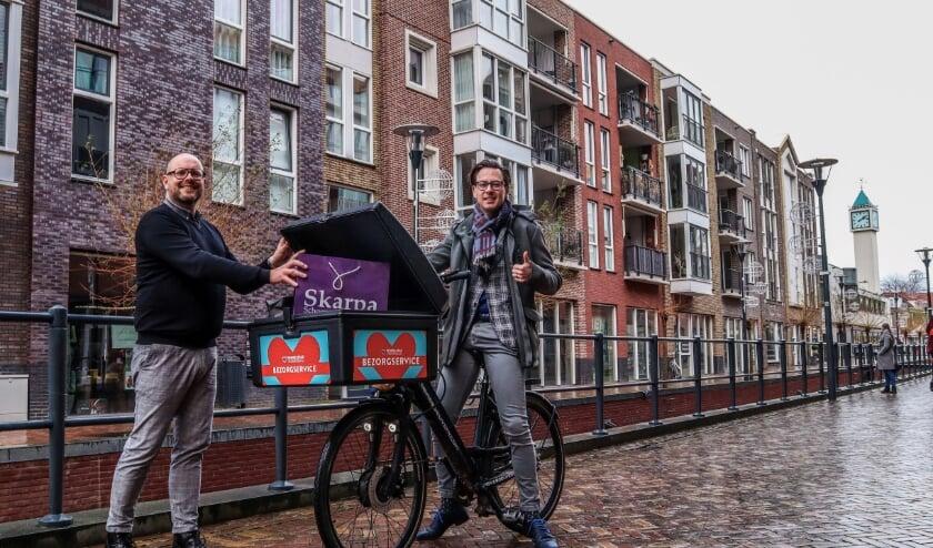 <p>Winkelstadmanager Henny Jansen met wethouder Dylan Lochtenberg die het eerste pakketje op de fiets bezorgde. (Foto: Winkelstad Veenendaal)</p>