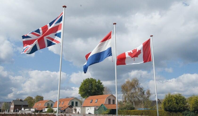 <p>De Nederlandse driekleur geflankeerd door de vlaggen van Engeland en Canada, onze bevrijders, met op de achtergrond de huizen van het 'Rode Dorp'.</p>