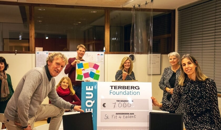 <p>Jan Terberg (links) reikte in de bibliotheek de cheque uit aan Jacqueline Koster (rechts), in aanwezigheid van mede-Foundationlid Freek, docenten en organisatoren van Fit4Talent. (Foto: Terberg Foundation)</p>