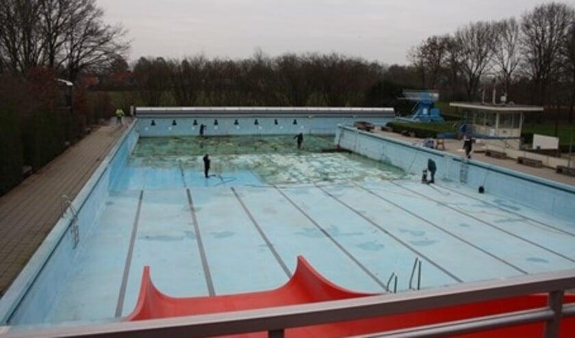 <p>Een zaterdagochtend met sneeuw op komst: vrijwilligers desondanks met hogedrukspuit aan de slag, om het wedstrijdbad schoon te maken.</p>