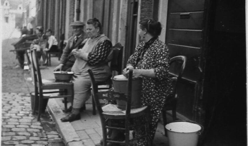 <p>In de Koningstraat schillen huisvrouwen de aardappels voor het avondeten,1940. Foto: uit de collectie van het Volksbuurtmuseum</p>