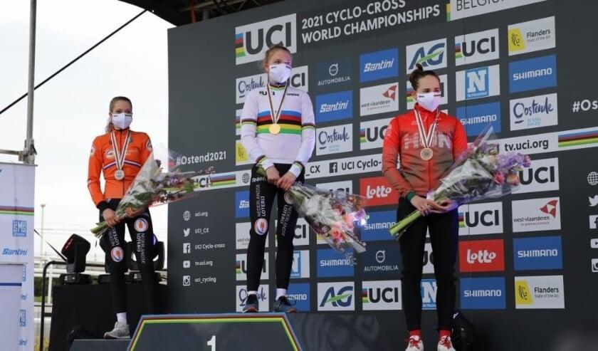 <p>Aniek van Alphen (l) neemt de tweede plaats in op het erepodium tijdens de wereldkampioenschappen veldrijden in Oostende.&nbsp;</p>
