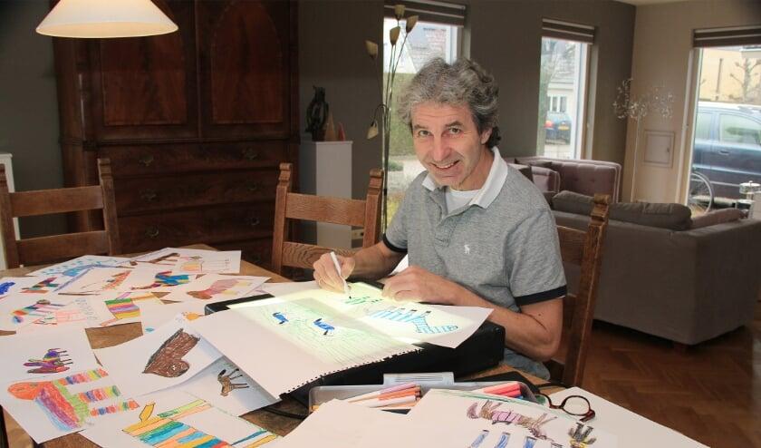 <p>Maarten van der Geest te midden van kindertekeningen die hem inspireren bij het maken van sculpturen voor het kunstwerk.</p>