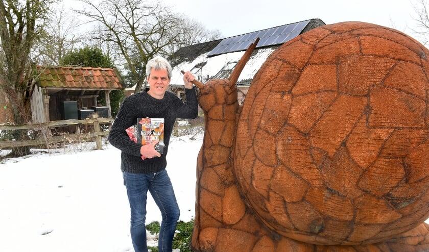 <p>Maurits Steverink in zijn moestuin bij de mega slak, het symbool van de Slow Food beweging (foto: Roel Kleinpenning)</p>