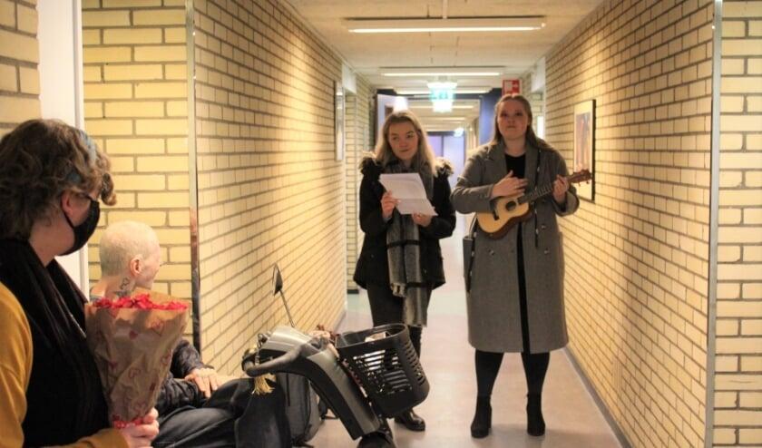 Studenten Nica en Anne brengen een lied aan de heer Westelaken.