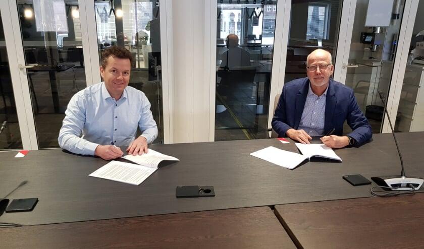 <p>Burgemeester Arend van Hout (rechts) en Jeroen van den Adel van AdVicus BV tekenen de koopovereenkomst.</p>