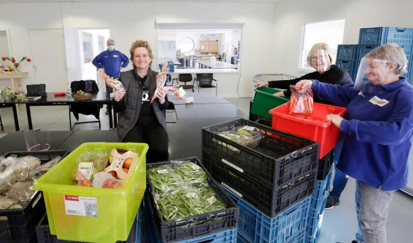 <p>Samen met enkele vrijwilligers laat Mari&euml;tte de zakken snoep zien die door de stichting Striepersgat werden geschonken. Foto: Jurgen van Hoof.</p>