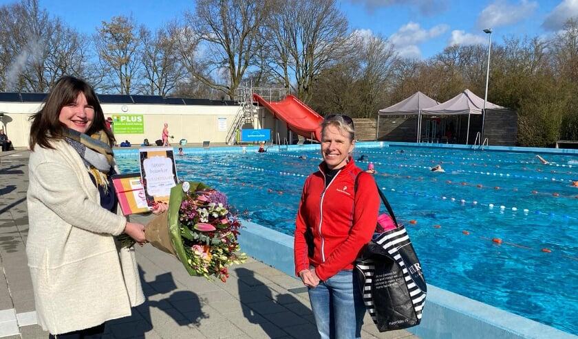 <p>Uit handen van Corina IJkhout (VakantieXperts Bennekom) ontvangt Marjolein Foppen een bos bloemen, een waterdichte tas en een 10 badenkaart als 5000e bezoeker van Zwembad de Vrije Slag deze winter.</p>