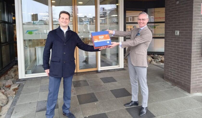 <p>André Flach (links), kandidaat Kamerlid SGP bezorgt stroopwafels bij Blije Borgh en Nebo.&nbsp;</p>