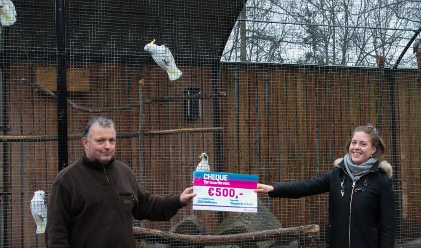 <p>Eigenaar Richard Loomans ontvangt de cheque van 500 euro voor de verzorging van de dieren van zijn ZOO Veldhoven. FOTO: De Schalm.&nbsp;</p>