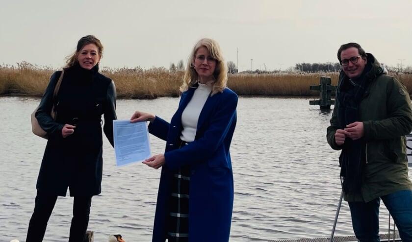 <p>Wethouder Antoinette Ingwersen (links) en en wethouder Rein Kroon (rechts) overhandigen de brief aan Mona Keijzer Foto: gemeente Nieuwkoop</p>
