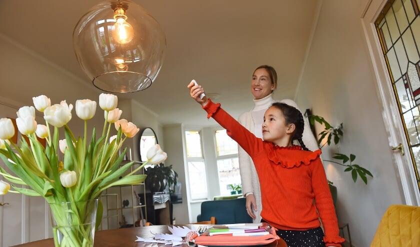 Maartje Gosselink ziet hoe dochter Annabelle Tan (8 jaar) de slimme verlichting bedient. (foto: Roel Kleinpenning)