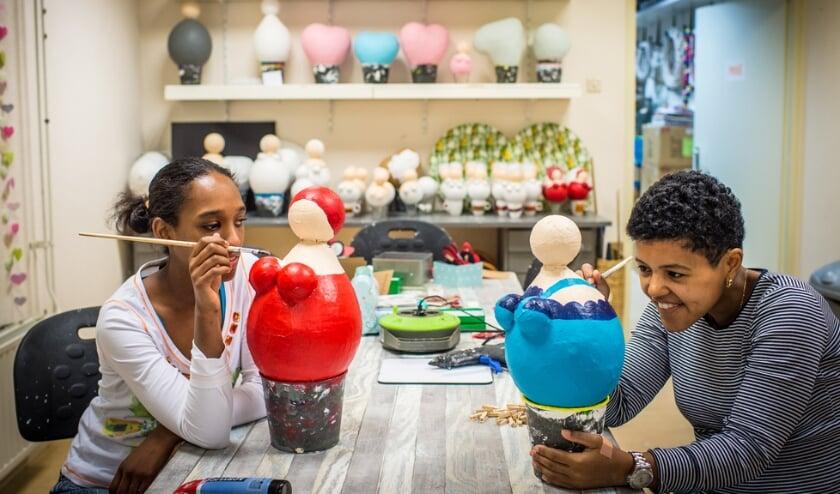 <p>Sharon en Gabri&euml;lla werken aan poppen van papier-mach&eacute; die in de webwinkel te koop zijn. Gabri&euml;lla: &ldquo;Dat doe ik al heel lang. Ik vind er alles leuk aan en het is niet moeilijk. Ik vind het ook geweldig dat ze verkocht worden in de webwinkel.&quot; (Foto: pr)</p>