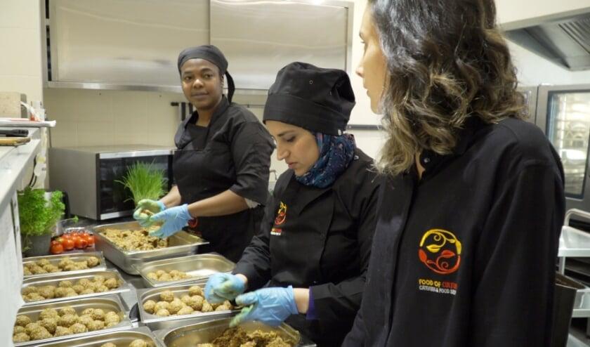 <p>Mahan Eslami (rechts), oprichtster van &#39;Delen smaakt beter&#39;, bezig met het bereiden van maaltijden.&nbsp;</p>