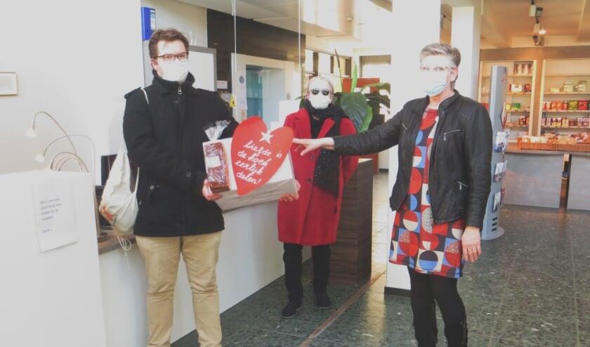 SP'ers Jan Breur en Alja Berck overhandigen een doos met lekkers op de Engelenburg.