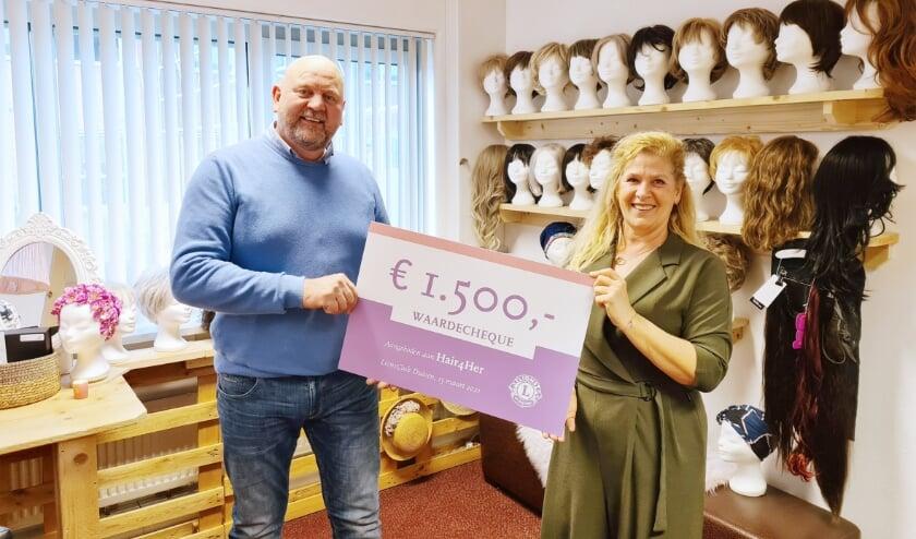 <p>Ronald Gerressen van Lionsclub Duiven reikt de cheque uit aan Esther Hogeweg van Hair4Her.</p>