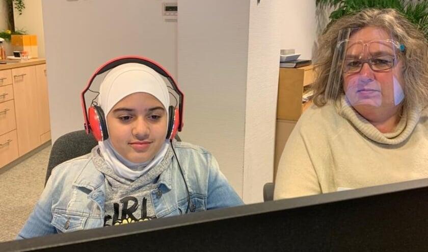 <p>Ingrid aan het werk met een van haar leerlingen. Door mee te kijken ziet ze waar de jongeren mee bezig zijn en kan ze tijdig bijsturen.</p>
