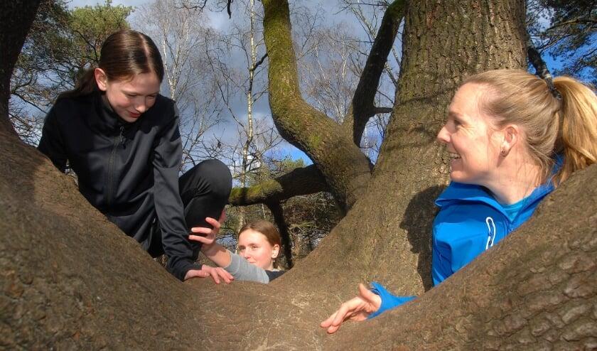 <p>Noa en Izzy klimmen in een boom terwijl Carmen toekijkt.</p>