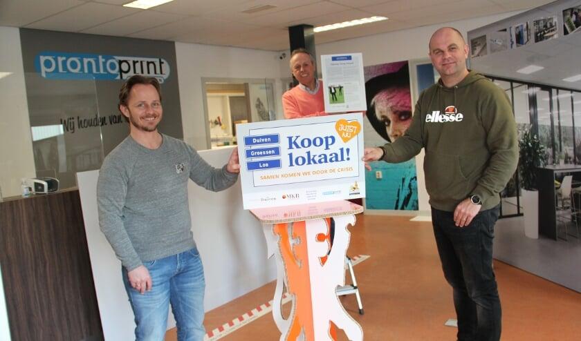 <p>Drukker Robert de Wit van Pronto Print, Theo de Reus van MKB Duiven en centrumondernemer Peter Houthuijzen (v.l.n.r.) presenteren de poster.</p>