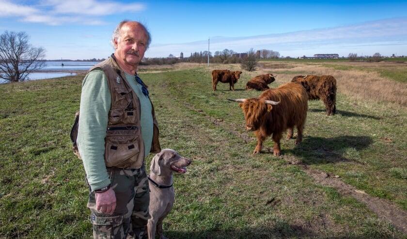 Huib Wijzenbroek met zijn hond Roza bij de Schotse Hooglanders in de Kleine Willemswaard bij Tiel. Maart 2021, foto Jan Bouwhuis.