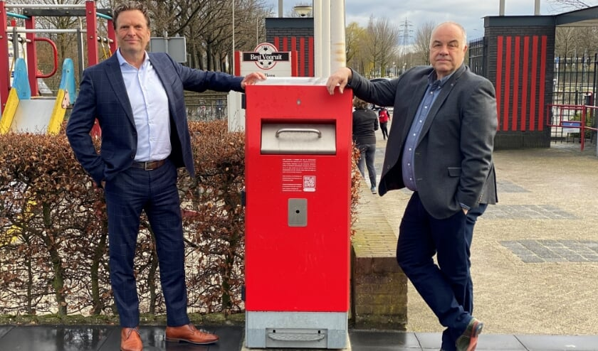 <p>Jan Pieter Been (links) en Mat Gerrits poseren trots bij de WasteMates die een prominente plek hebben gekregen op het sportcomplex.</p>