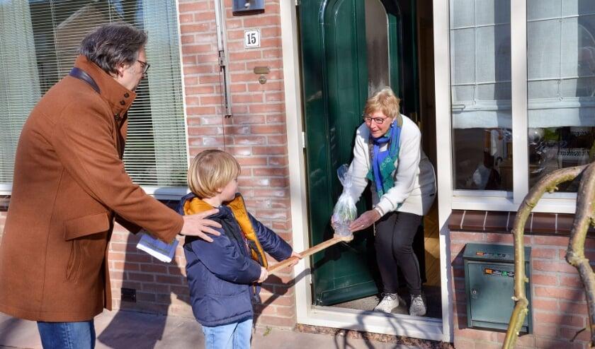 <p>Gemeenteraadslid Han Bovens bezorgt met zoon Faas coronaproof een Lentegroet bij mevrouw Marée-Vergeer.&nbsp;<br>Foto: Paul van den Dungen</p>