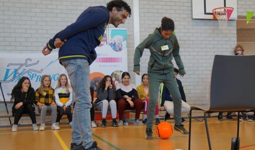 <p>Leerlinge Malak voert een voetbaltruc uit met behulp van een voetbalapp, terwijl ze gecoacht wordt door Touzani.</p>