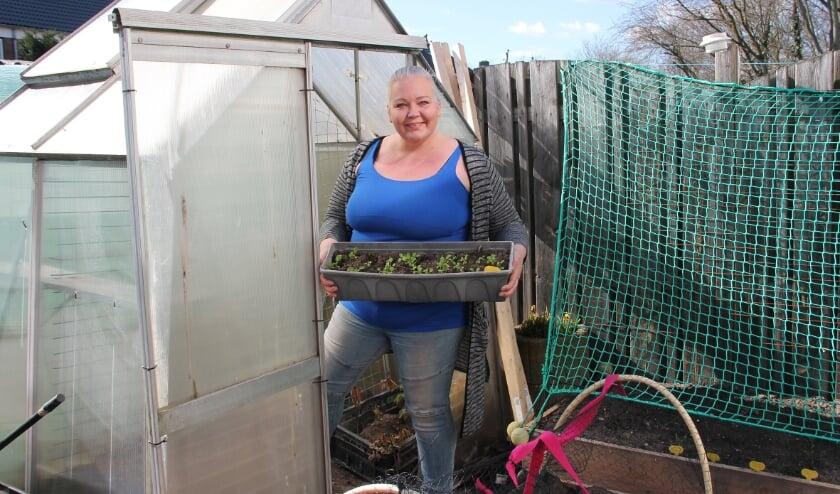 <p>Dominique Verheul met bakken in de weer in haar moestuin, die ze aan het ombouwen is naar een tasttuin.</p>
