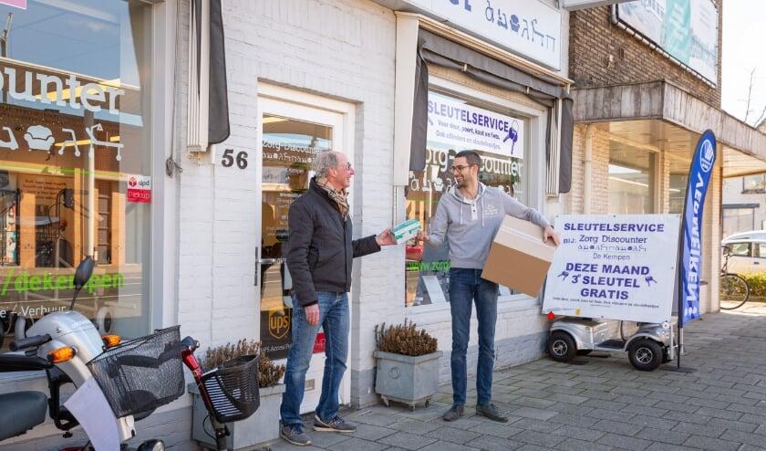 Bert Waterschoot (l) is blij met de mondkapjes voor klanten van de Voedselbank