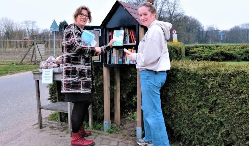 <p>Felia van Roekel met dochter Sanne vullen de mini-bibliotheek weer aan. (Foto: Jan van den Brink).</p>