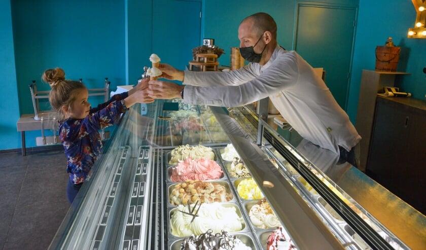 <p>Tijdens de opening van Daan&#39;s Droomijs schept Andr&eacute; Lammerse twee ijsjes voor buurmeisje Roos. &nbsp; Foto: Paul van den Dungen</p>