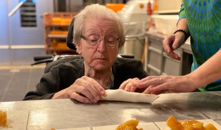 <p>Vier bewoners van woonzorgvoorziening Kanidas in Best hebben samen met Teun Toebes appelflappen gebakken.</p>