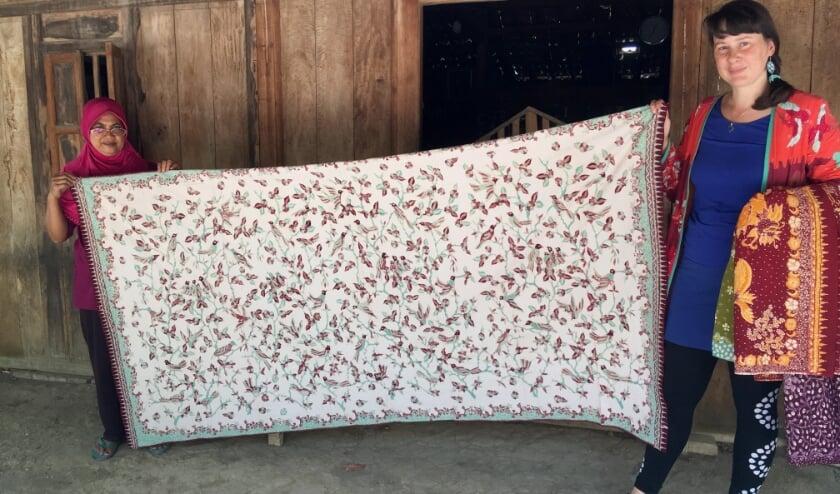<p>Sabine Bolk (rechts) toont een prachtig stuk handgemaakte batik uit Lasem. Sabine verzorgt op 22 april ook een webinar over dit onderwerp.</p>