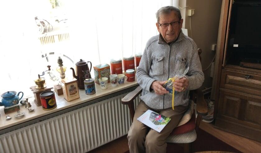 <p>Jan Kuster is blij met het vogelhuisje dat hij net heeft gekregen van de vrijwilliger van De Zonnebloem.</p>